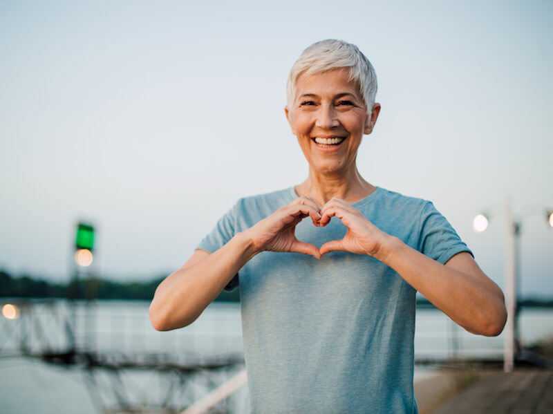 Woman improving her life expectancy by wearing hearing aids and working out is outside on a pier.