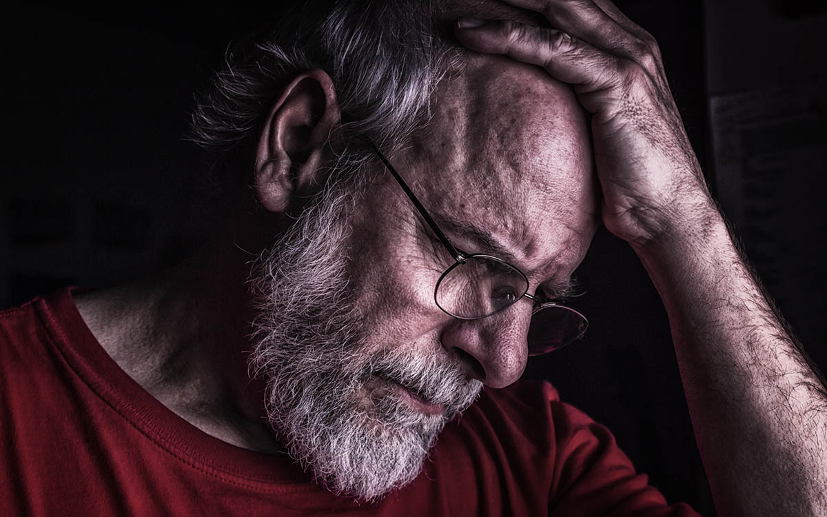 Man having trouble remembering things because of brain strain related to hearing loss.