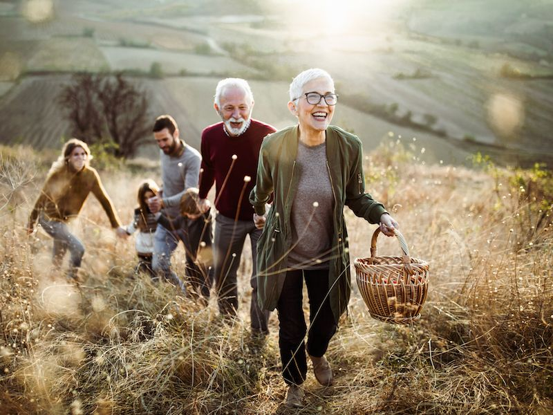 Woman wearing hearing aids climbing hill with family and laughing at a joke.