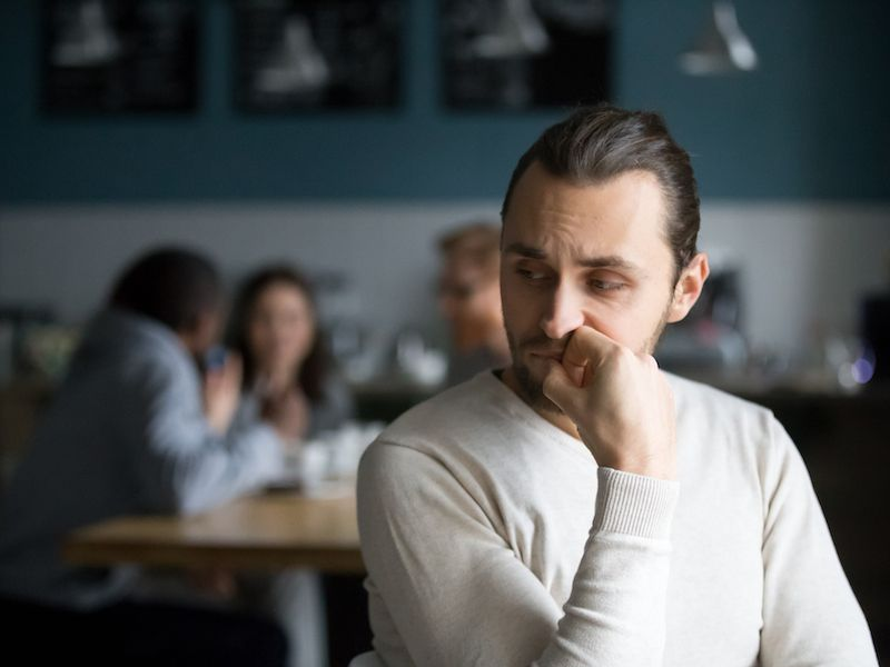 Man isolated and depressed in a cafe because he has hearing loss.