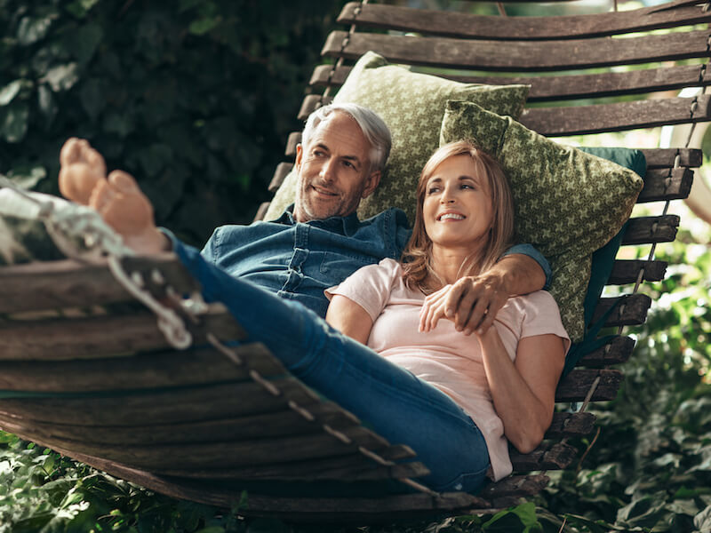Man who got rid of tinnitus using a hearing aid on a hammock with his wife.
