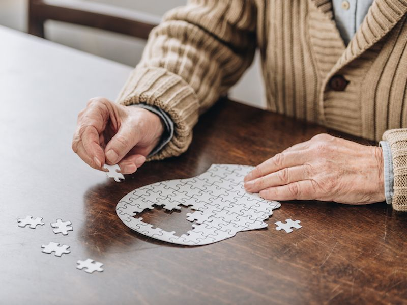 Woman with hearing loss gets hearing aid to slow down her dementia and completes a puzzle.