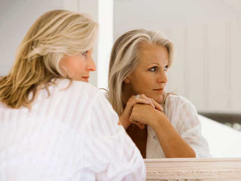 Woman considering hearing aids as she looks at her image in a mirror.