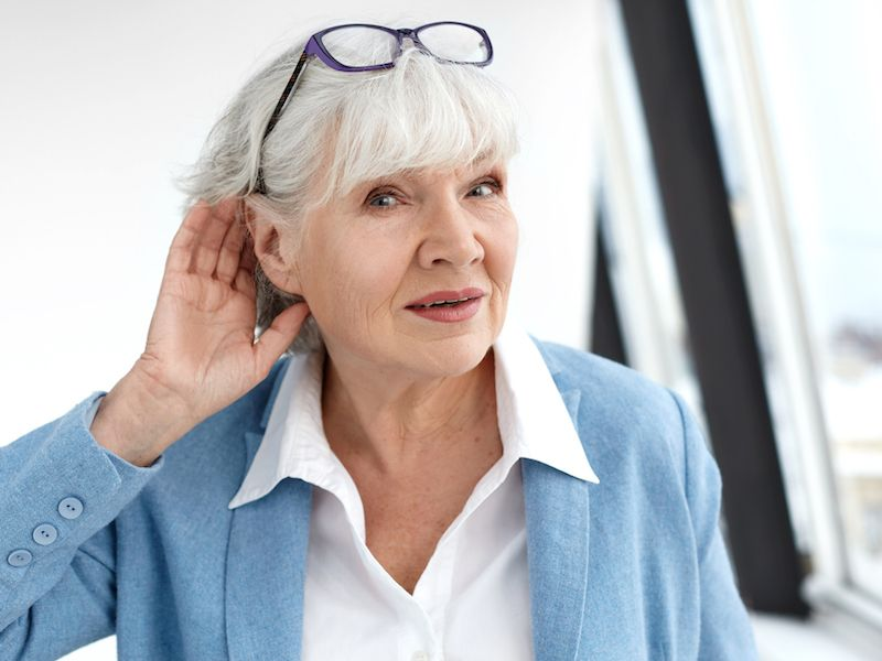 Woman holding ear because her hearing aid isn't working.