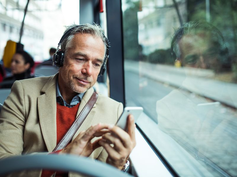 Man on bus wearing headphones unaware he is causing hearing loss with prolonged exposure.