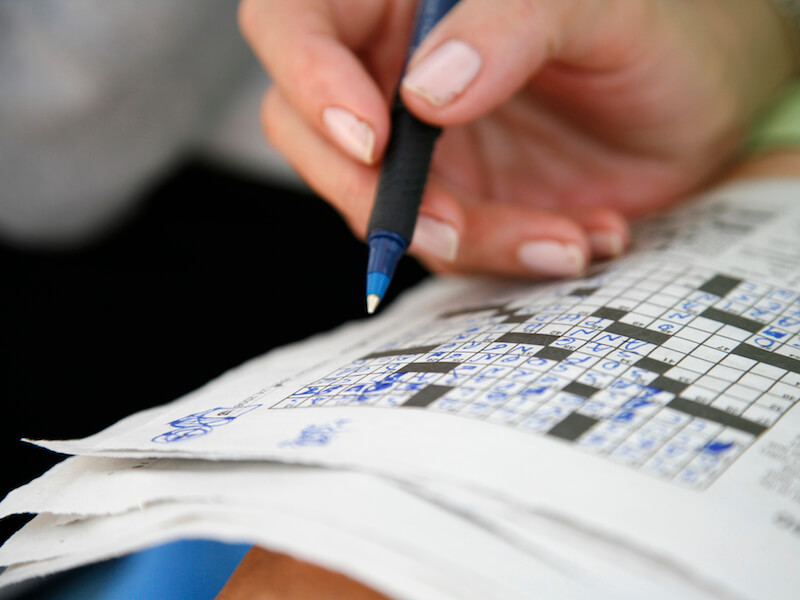 Woman struggling with a crossword puzzle because she has hearing loss induced memory loss.