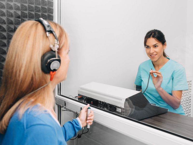 Woman getting her hearing test to see if she has hearing loss.