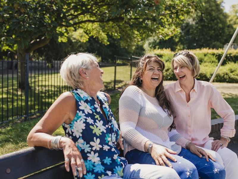Women with hearing loss laughing on park bench.