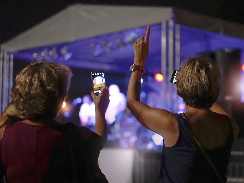 Women enjoying a summer concert with hearing protection.