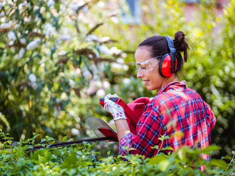 Woman protects her hearing with ear muffs while doing yardwork.
