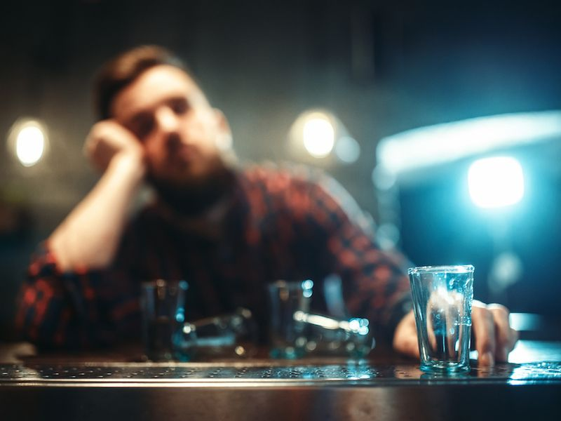 Young man with hearing loss drinking more alcohol than he should.