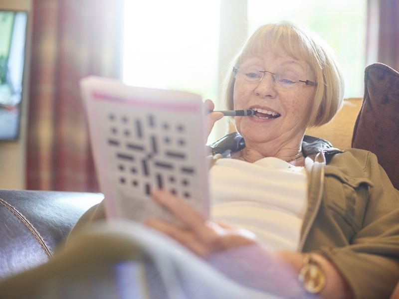 Woman doing crossword puzzle and wearing hearing aid to improve her brain.