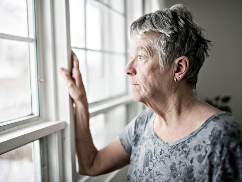 Woman at the window looking out and feeling isolated from untreated hearing loss.