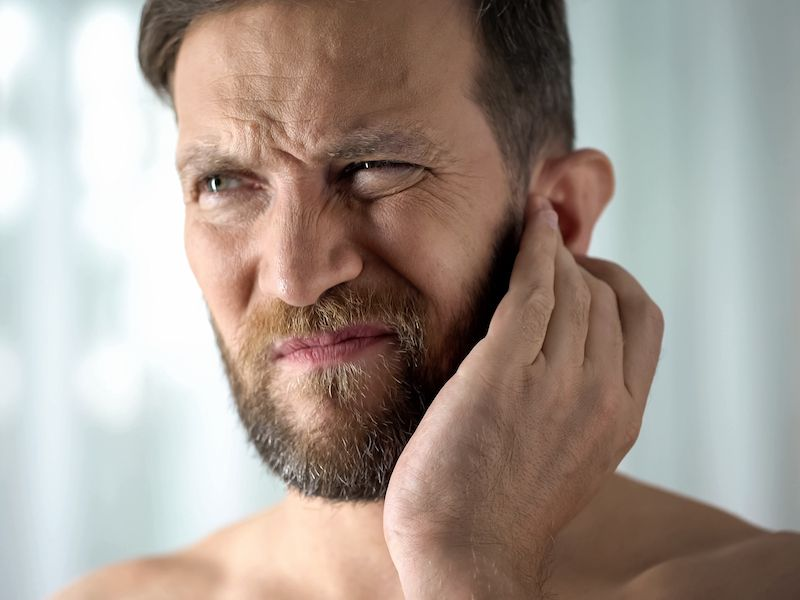 Man touching ear in response to crackling noises in his ear.