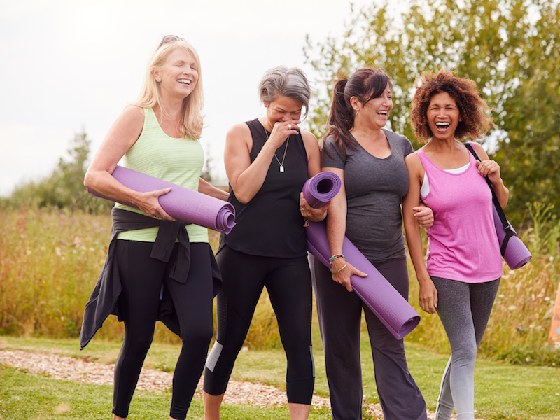 Woman enjoying yoga with her friends after getting fit with hearing aids.