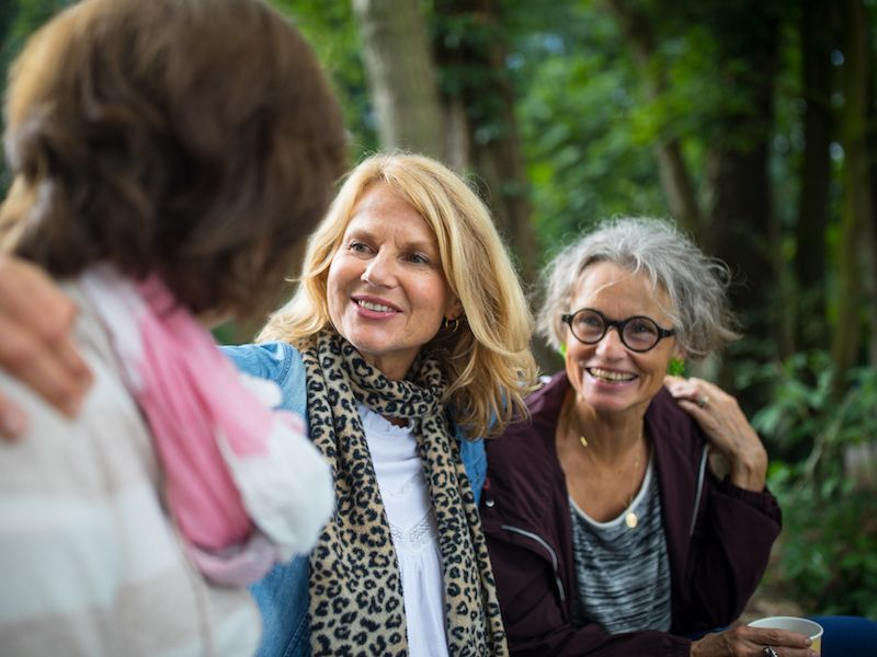 Woman wearing hearing aids enjoys a hike with friends.