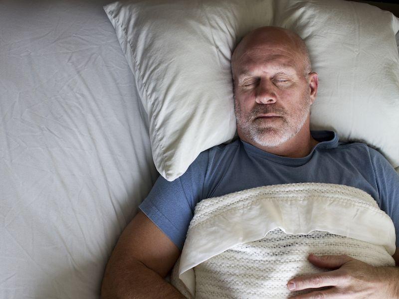 Man with hearing loss sleeping better because he has hearing aids.